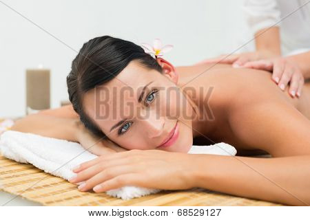 Peaceful brunette enjoying a back massage smiling at camera in the health spa