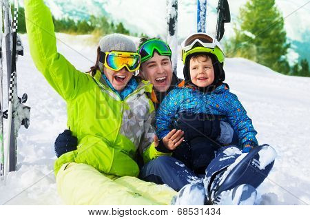 Happy parents and boy with ski masks sit on snow