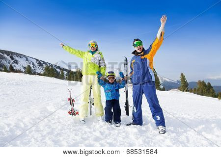 Happy parents in ski masks hold hands of son