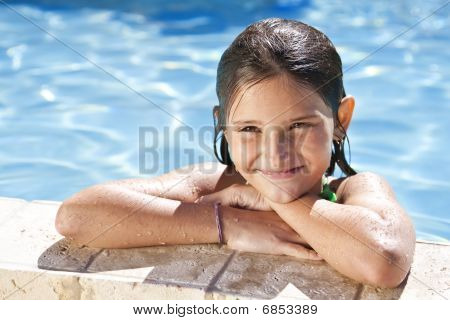 Happy Girl Leaning On The Edge Of A Swimming Pool