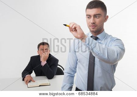 Young businessman holds marker writing, drawing something in the