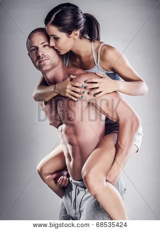 Shirtless boyfriend giving sweet girlfriend piggy back ride