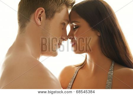 Loving young couple tenderly embracing touching foreheads and noses, head and shoulders profile view on white