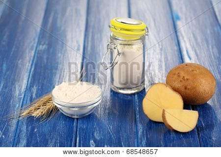 Starch in bowl and bank on wooden table close-up