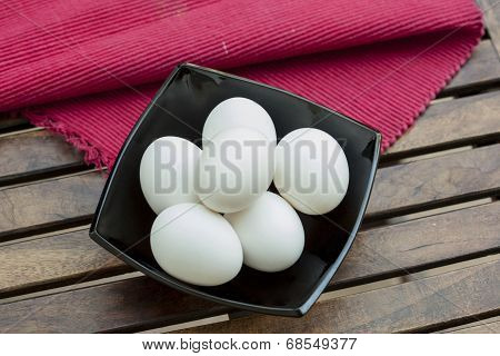 Eggs in a black bowl isoated on wooden table.