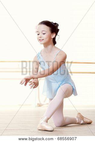 Little dancer doing exercises in ballet studio