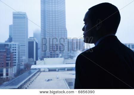 Empresário, olhando através de uma janela