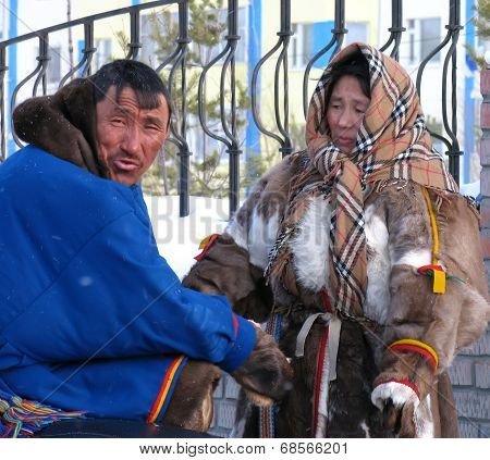 Nadym, Russia - March 11, 2005: Unknown Man And Woman - Nenets Sitting In The Street.