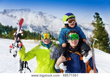 Parents and child on dad's shoulders in ski masks