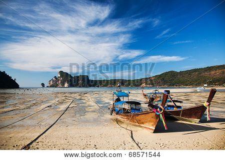 Tropical beach, traditional long tail boats at low tide in Ko Phi Phi bay, Andaman Sea, Thailand
