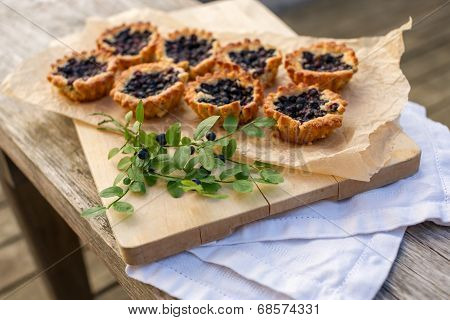 Eight Small Homemade Blueberry Pies On Wooden Table.