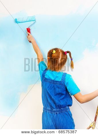 Little girl in blue bib and brace paints the wall