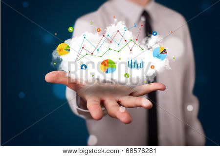 Young businessman presenting cloud with charts and graph icons and symbols
