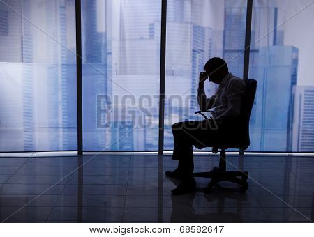 Tensed Businessman Sitting On Chair By Office Window