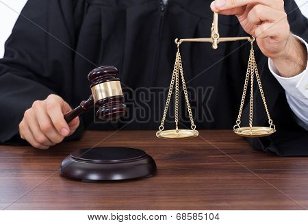 Judge Holding Weight Scale While Striking Gavel At Desk
