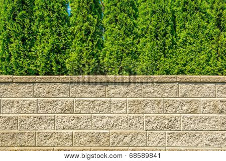 Stone fence with green lawn and landscape