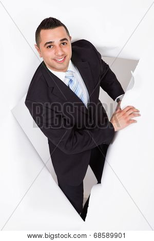 Businessman Emerging Through White Wall