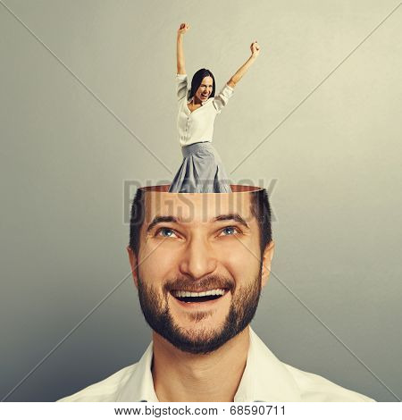 laughing young businessman with open head. young excited businesswoman dancing and raising hands up in the man's head. photo over grey background