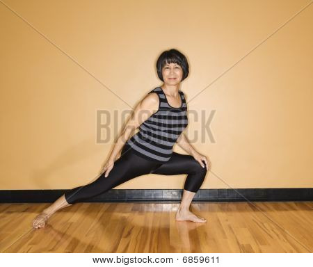 Woman Stretches Leg In Yoga Pose