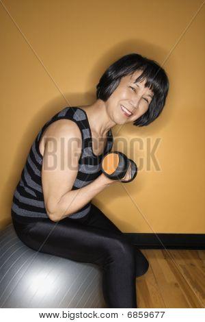 Woman On Balance Ball Lifting Weights