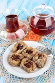 stock photo of baklava  - Sweet baklava on plate with tea on table - JPG