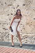 foto of vivacious  - Candid image of a laughing vivacious elegant young woman in a white summer dress and high heels carrying a clutch purse standing in front of an old stone building - JPG