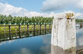 picture of bollard  - Closeup of a weathered oak bollard with flaking off white paint and a wooden jetty reflected in the mirror smooth water surface of a Dutch canal - JPG