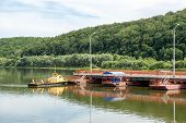 image of pontoon boat  - tug boat sets section of pontoon bridge on the river Oka  - JPG