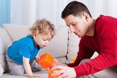 image of babysitting  - Man and little boy playing with toys together - JPG