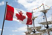 stock photo of historical ship  - The close view of Canadian flag with historic ship masts in a background  - JPG