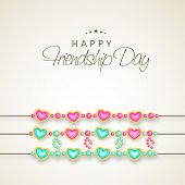 stock photo of friendship day  - Happy Friendship Day celebrations concept with heart shape decorated band on shiny brown background - JPG