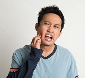 stock photo of toothache  - Asian male toothache with painful expression - JPG