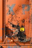 foto of boxcar  - A section of a rusted boxcar shows major corrosion while exhibiting a panel full of texture and color - JPG