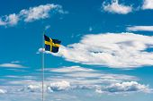 picture of sweden flag  - Swedish flag with the flag in front in focus on a typical summer sky in Sweden - JPG