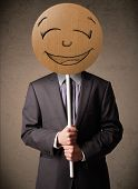 picture of emoticons  - Businessman holding a cardboard smiley face emoticon in front of his head - JPG