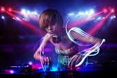 pic of disc jockey  - Pretty young disc jockey girl playing music with light beam effects on stage - JPG