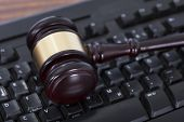 stock photo of courtroom  - Closeup of mallet on computer keyboard in courtroom - JPG