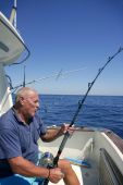stock photo of game-fish  - Angler elderly big game sport fishing boat blue summer sea sky - JPG