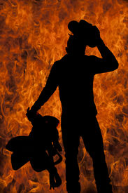 stock photo of western saddle  - a silhouette of a cowboy with a fire background holding on to his hat and saddle - JPG
