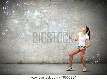 Young pretty girl in shorts and shirt playing imaginary guitar