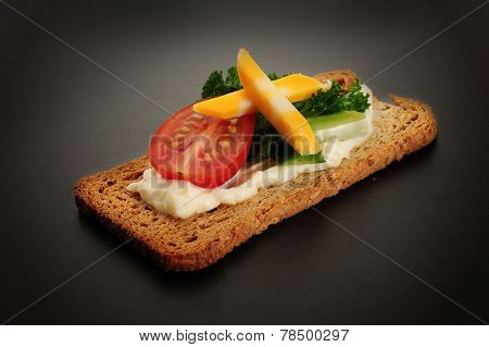 Close-up image of crackers with some cream tomato, cucumbers and cheese