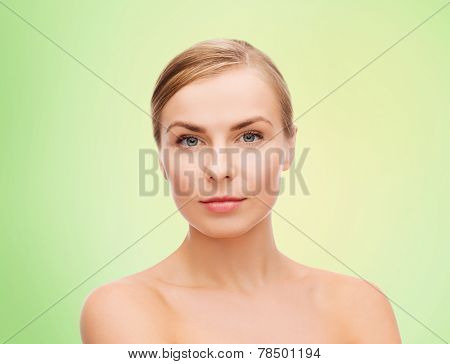 beauty, people and health concept - beautiful young woman with bare shoulders over green background