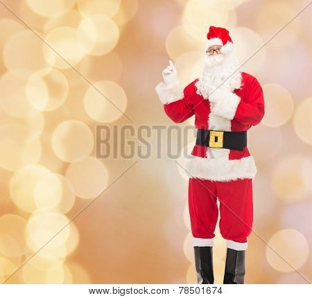 christmas, holidays, gesture and people concept - man in costume of santa claus pointing fingers over beige lights background