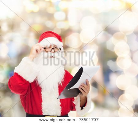 christmas, holidays and people concept - man in costume of santa claus with notepad over lights background
