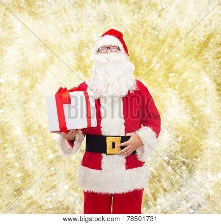 christmas, holidays and people concept - man in costume of santa claus with gift box over yellow lights background