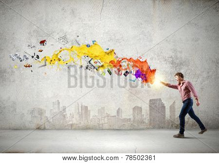 Young man in casual throwing colorful paint splashes