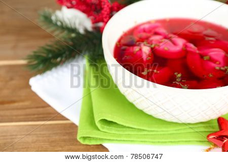 Traditional polish clear red borscht with dumplings and Christmas decorations on wooden table background