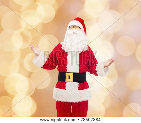 christmas, holidays and people concept - man in costume of santa claus over beige lights background