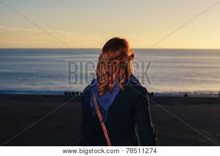 Woman Admiring The Sea At Sunset