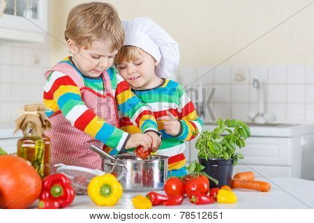 Two Cute Little Kid Boys Cooking Italian Soup And Meal With Fresh Vegetables